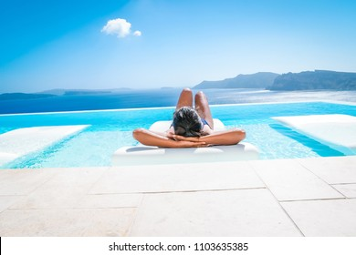 young woman at an luxury infinity swim pool looking out over the caldera of Santorini Greece, bright summer holiday Santorini poolside