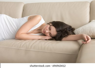 Young woman lying asleep on couch, sleeping attractive girl taking nap at home, resting on arm on comfortable sofa, exhausted teenager dozing after sleepless night, feeling lack of sleep deprivation