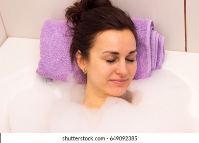 Young woman lying in the bath