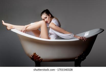Young woman lying in bathtub and looking away. Beautiful female relaxing in bathtub. Girl in bathtub. Pleasant woman taking pleasure in bath