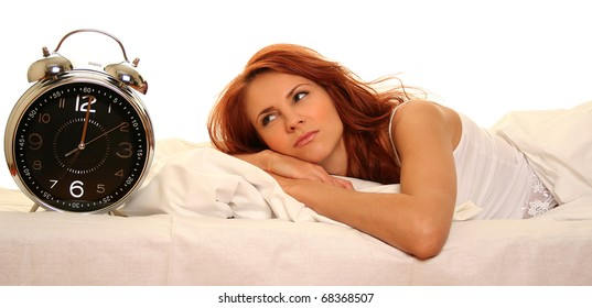 young woman lying in bed with alarm clock