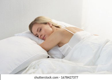 Young woman lying in the bed. Beautiful blond sleeping girl. Morning in the bedroom, daylight from the window. Health and rest.