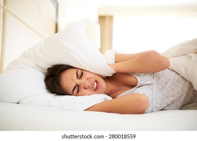 Young woman lying in bed covering ears with pillow annoyed by noise.