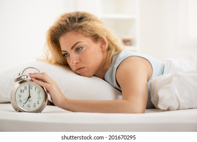 Young woman lying in bed in the morning. She is waking up with alarm clock.