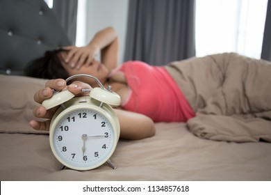 Young woman lying in bed suffering from sound covering head and ears with making unpleasant face. early wake up not getting enough sleep , Women feel irritated when they hear the alarm clock