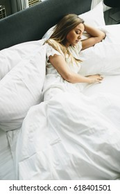 Young woman lying in bed with white linen