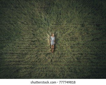Young woman lying down in the middle of a field and relaxing (drone photo).
