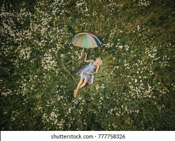 Young woman lying down in the middle of a meadow and holding umbrella (drone photo).