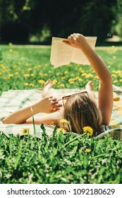 Young woman lying down on a blanket in home yard and sunbathing on a sunny day and reading a real book. Grass and dandilion background, nice vintage look.
