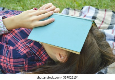 Young woman lying down and relaxing with book over her face.Woman reading a book and covering her face