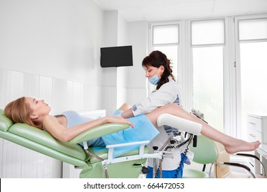 Young woman lying in gynecological chair during gynecological checkup with her doctor