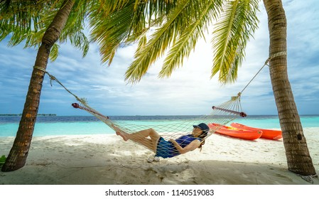 Young woman lying in a hammock on the beach