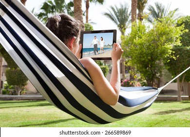 Young Woman Lying In Hammock Watching Video On Digital Tablet