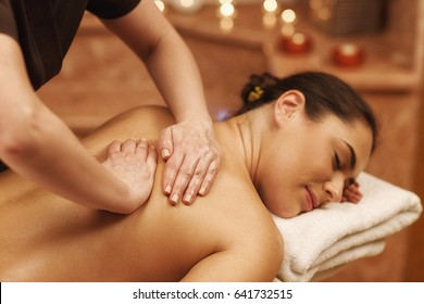 Young woman lying with her eyes closed relaxing during back massage at beauty salon. Professional masseuse working with her client. Beautiful girl having back massage at spa center hotel resort