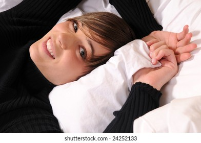 Young woman lying in a hotel bed surrounded by pillows