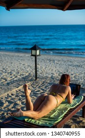 A young woman is lying with a laptop on a deckchair near the sea. work in travel. freelancer