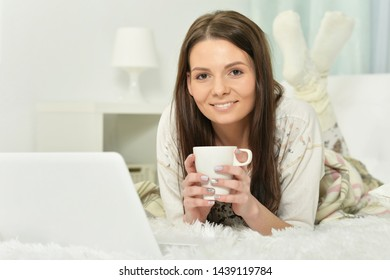 Young woman lying on bed with cup of coffee