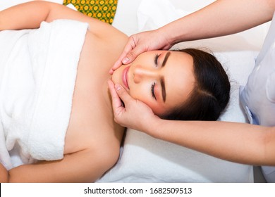 Young woman lying on the bed and masseuse use two hand to face massage with young female at beauty spa for blood circulation and good health, copy space