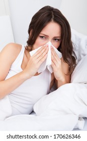 Young Woman Lying On Bed Infected With Allergy Blowing Her Nose