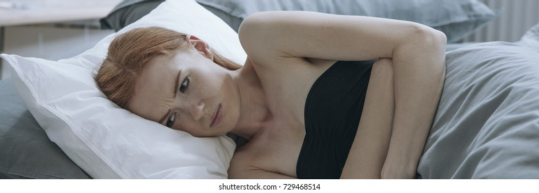 Young woman lying on the bed suffering from stomachache and painful period cramps