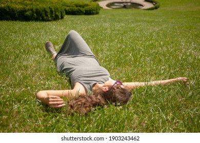 The young woman is lying on the big green lawn.