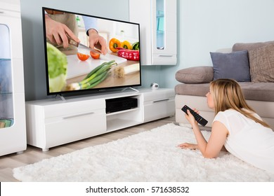 Young Woman Lying On Carpet Watching Cooking Show On Television At Home