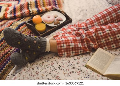Young woman lying on colorful bed having breakfast on holidays. Morning in a cozy warm bedroom with natural juice Christmas cookies and and donut. Happy young girl thinking on wishes for the new year