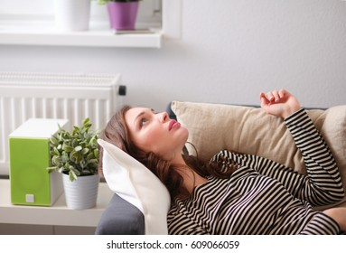 Young woman lying on a couch at home