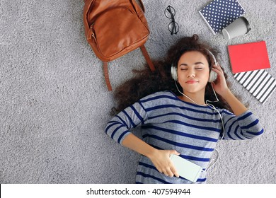 Young woman lying on the floor and listening to music