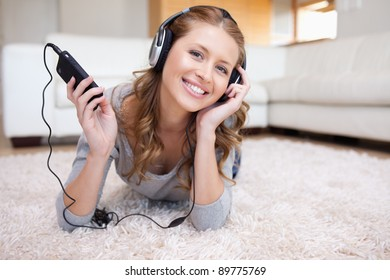 Young woman lying on the floor enjoying music