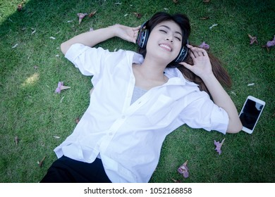 Young woman lying on grass floor listening music from moblie phone with headset. Girl chilling lifestyle relaxing. people with nature outdoor.
