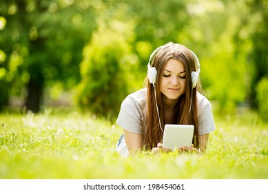 Young woman lying on the grass listening to music on her headphones that she has downloaded onto her tablet or MP3 player as she enjoys the tranquility of a lush green park