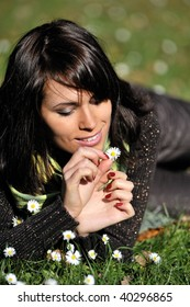 Young woman lying on a grass, group of daisies on a foreground