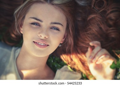 Young woman lying on grass portrait. Focus on eyes.