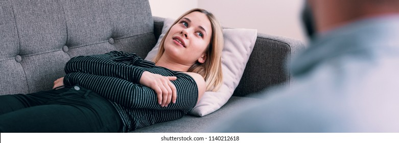 Young woman lying on a gray sofa at a therapy session, talking about her problems and looking up at her psychotherapist
