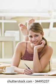 A young woman is lying on her stomach and writing in a book.  She is smiling at the camera.  Vertically framed shot.