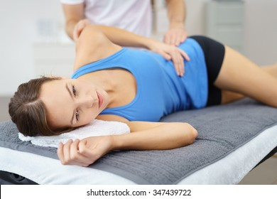 Young Woman Lying on her Side on bed While the Physical Therapist is giving a Treatment to her Injured Body.