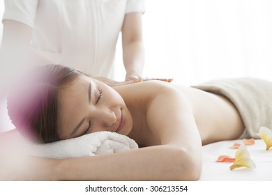 Young woman lying on massage table at spa