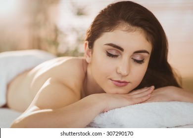 Young woman lying on massage table in therapy room
