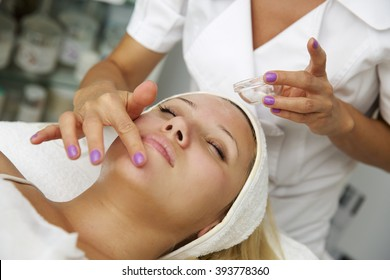 Young woman lying on massage table receiving face massage. Beauty treatment concept.