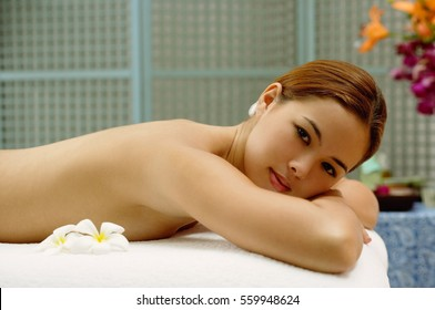 Young woman lying on massage table, looking at camera