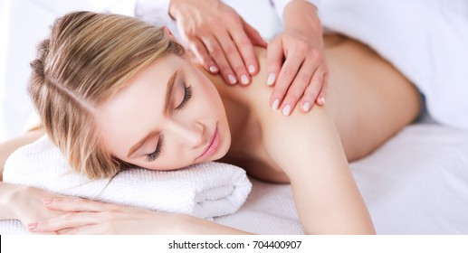 Young woman lying on a massage table,relaxing with eyes closed