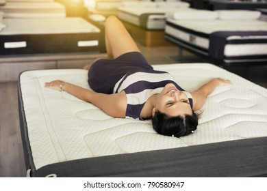 Young woman lying on new mattress in the furniture shop