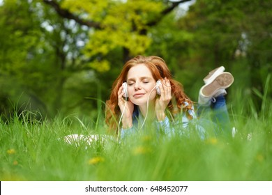 Young woman lying on a rug in fresh green spring grass enjoying her music in a park listening on headphones with closed eyes and a blissful smile, low angle view