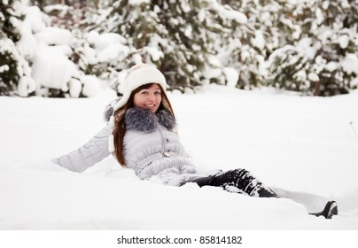 Young woman lying on the  snow in winter