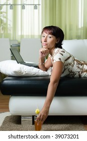 a young woman is lying  on a sofa, working on a notebook and drinking a juice