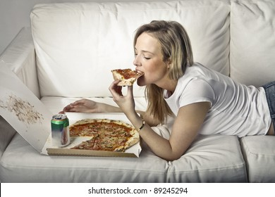 Young woman lying on a sofa and eating pizza