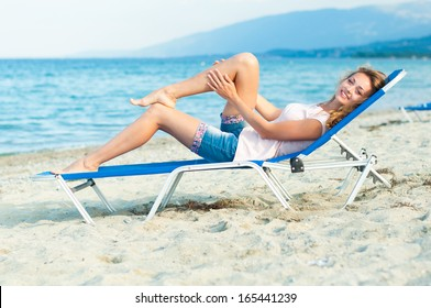 Young woman is lying on the sunbed at the seaside smiling