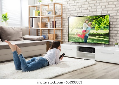 Young Woman Lying On White Carpet Holding Remote Control Enjoying Watching Television At Home