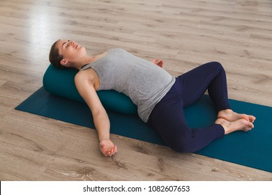 Young woman lying on yoga mat using bolster cushion